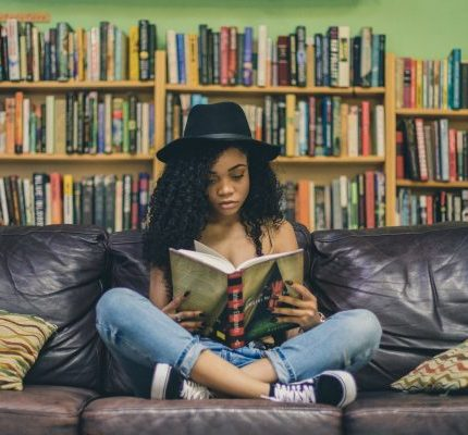 Girl Reading a Book on A Couch
